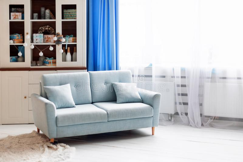 Blue sofa in white modern interior with Christmas decorations. Blue sofa in white modern interior with Christmas decorations stock images