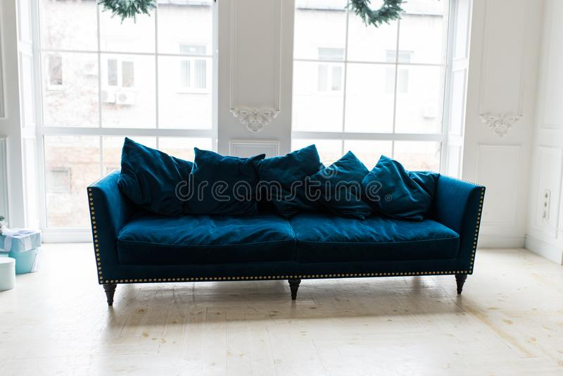 Blue sofa in white simple living room. Modern color of blue velvet couch. Interior royalty free stock images