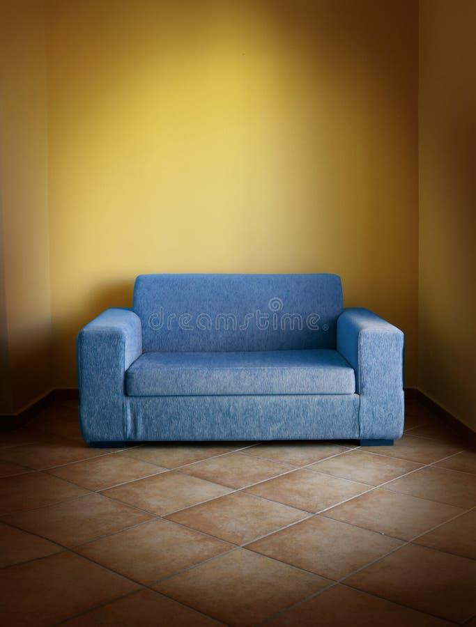 Blue sofa yellow wall stock photo