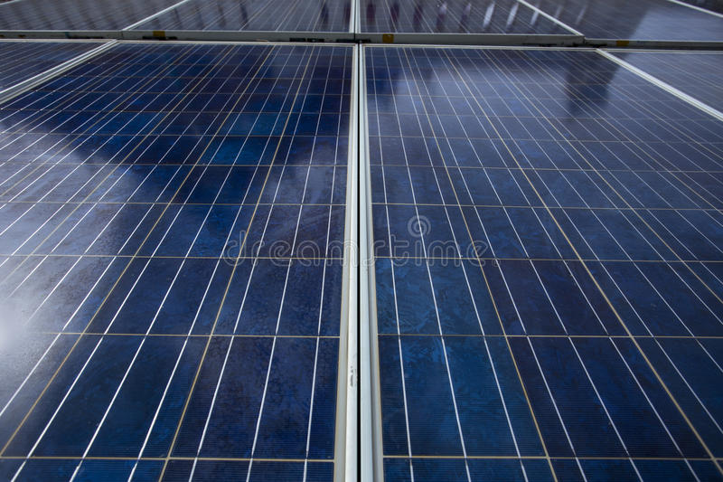 Blue solar cell panels that shown its surface grid line and textures. The panels are against sun light on noon time have shadow re stock image