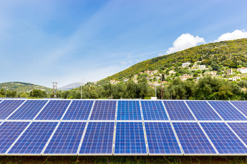 Blue solar collectors near town on mountain. Row of blue solar collectors near greek town on mountain royalty free stock images