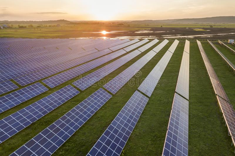 Blue solar photo voltaic panels system producing renewable clean energy on rural landscape and setting sun background.  stock image