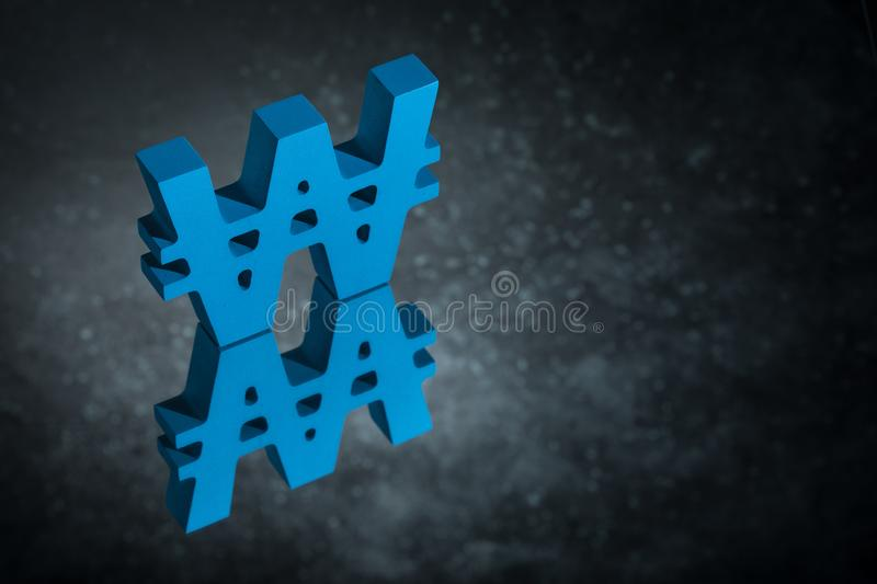 Blue Won Symbol or Sign With Mirror Reflection on Dark Dusty Background. Blue South Korean Currency Symbol or Sign Won With Mirror Reflection on Dark Dusty stock image