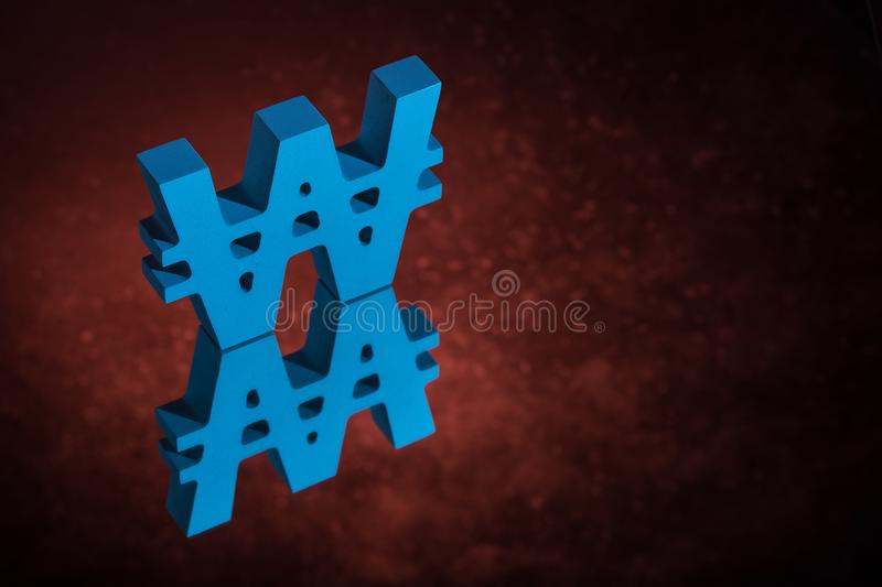 Blue Won Symbol or Sign With Mirror Reflection on Red Dusty Background. Blue South Korean Currency Symbol or Sign Won With Mirror Reflection on Red Dusty royalty free stock photo