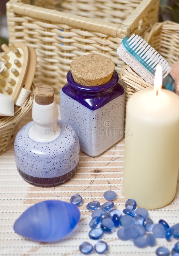 Blue spa pebbles. Blue composition of some spa items, blue colour dominating, blue ceramic vases, candle and some small blue pebbles royalty free stock images