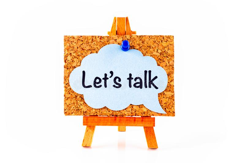 Blue speech bubble with phrase Let`s Talk on corkboard on wooden easel royalty free stock photo