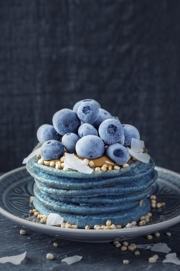 Blue spirulina pancakes. Topped with peanut butter, blueberries and coconut chips royalty free stock images