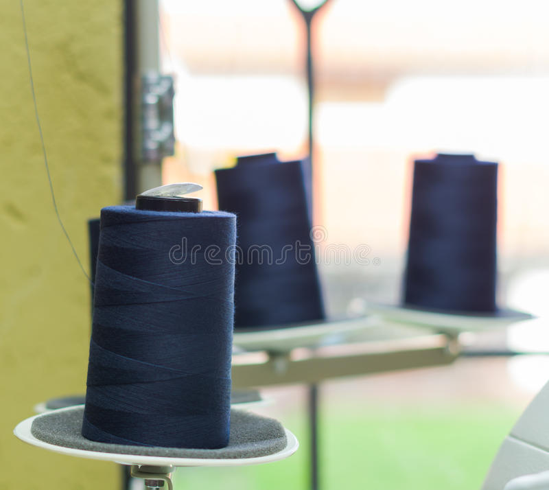 Blue spool of thread ready to be used in a sewing machine, behind other spools.  royalty free stock images