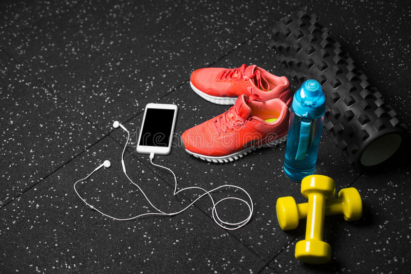 Yellow dumbbells, a pilates mat, blue bottle of water, sports shoes and white phone on a black floor background. stock photography