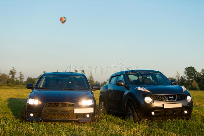 Blue sports car in a field and aerostat balloon at background. Blue sports car and gray crossover in a field and aerostat balloon at background at summer evening royalty free stock photography