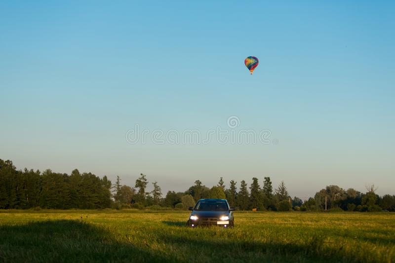 Blue sports car in a field and aerostat balloon at background. At summer evening royalty free stock photography