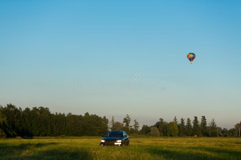 Blue sports car in a field and aerostat balloon at background. At summer evening royalty free stock images