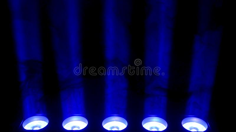 Blue spotlight and smoke on black background. Abstract dark background with bright blue stage spotlights. Lights and royalty free stock image