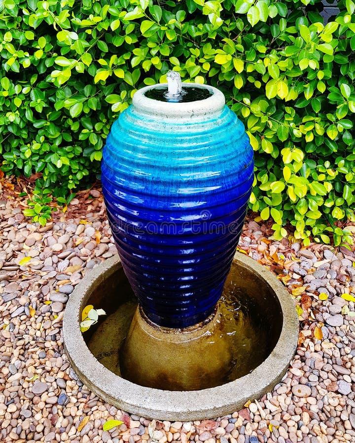 Blue spring pot at home garden. Pottery, vase, decoration, ceramics, art, design, trees, plant, shrub, pebble, grit, gravel, green, house, exterior, gardening royalty free stock photos