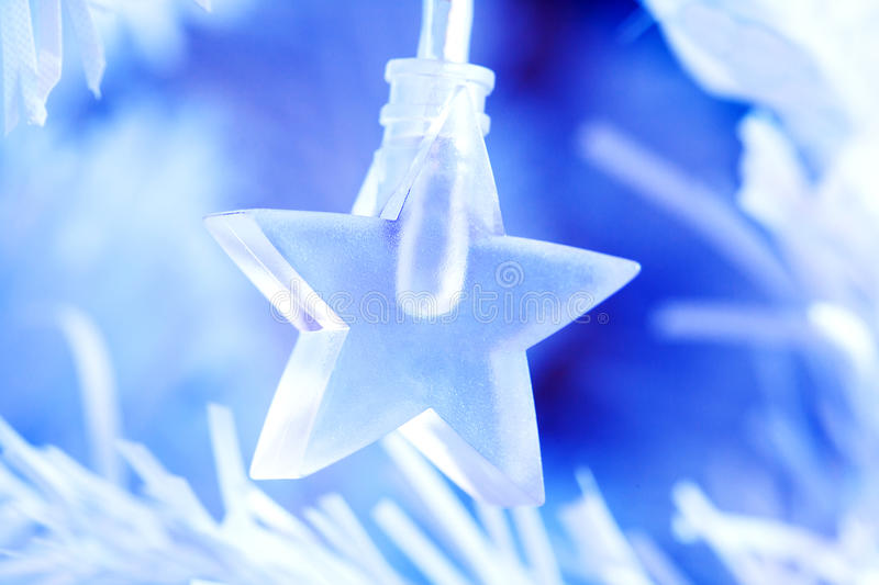 Blue star lighting. A clear blue star shaped plastic light bulb on the branch of an artificial Christmas tree royalty free stock images