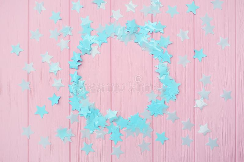 Blue stars confetti on a pink wooden background with round frame place for your text, design greeting cards and stock photography