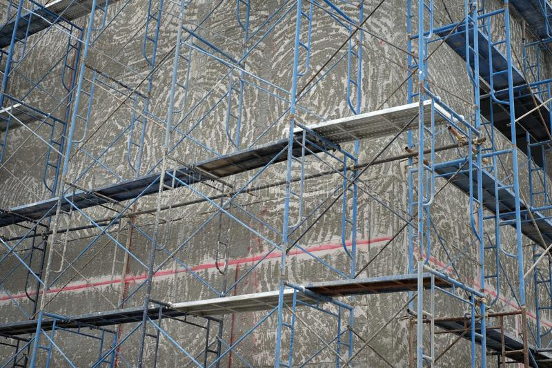 Steel scaffolding in front of the building. Blue steel scaffolding in front of the building being constructed royalty free stock image
