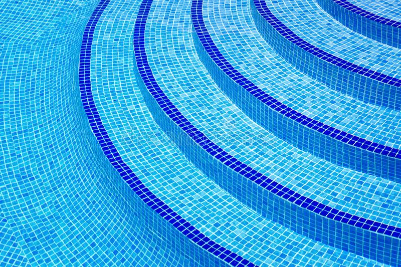 Blue steps stairway into swimming pool royalty free stock images
