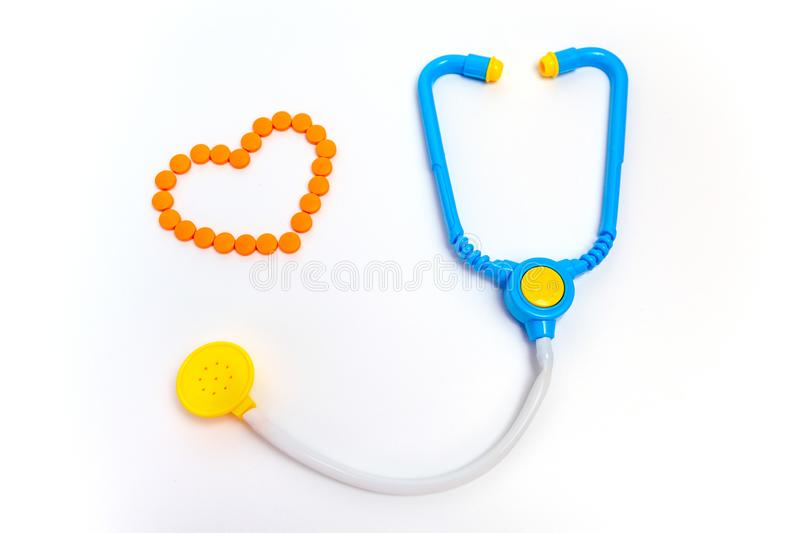 Blue stethoscope Isolated on white background. Medicine concept. Children`s toys by profession doctor. A heart is by orange pills stock photo