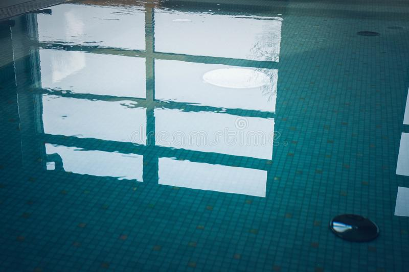 A Swimming pool. Blue still water in swimming pool with a reflection of windows visible stock image