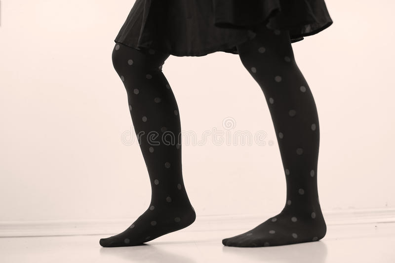 Blue stockings with beige dots. Woman legs wearing dark blue stockings with dots and a black skirt stock photography