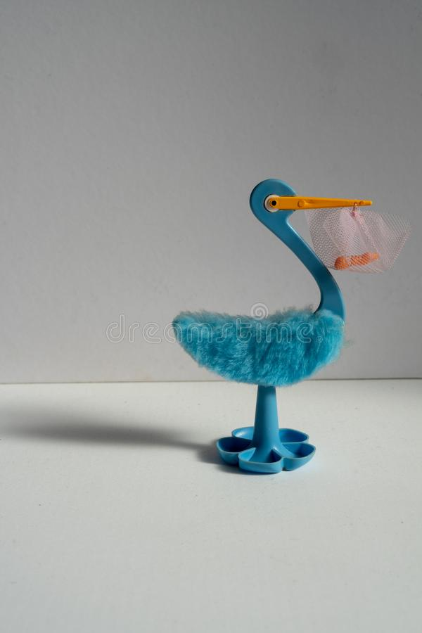 A blue stork with a baby on its beak. royalty free stock photo