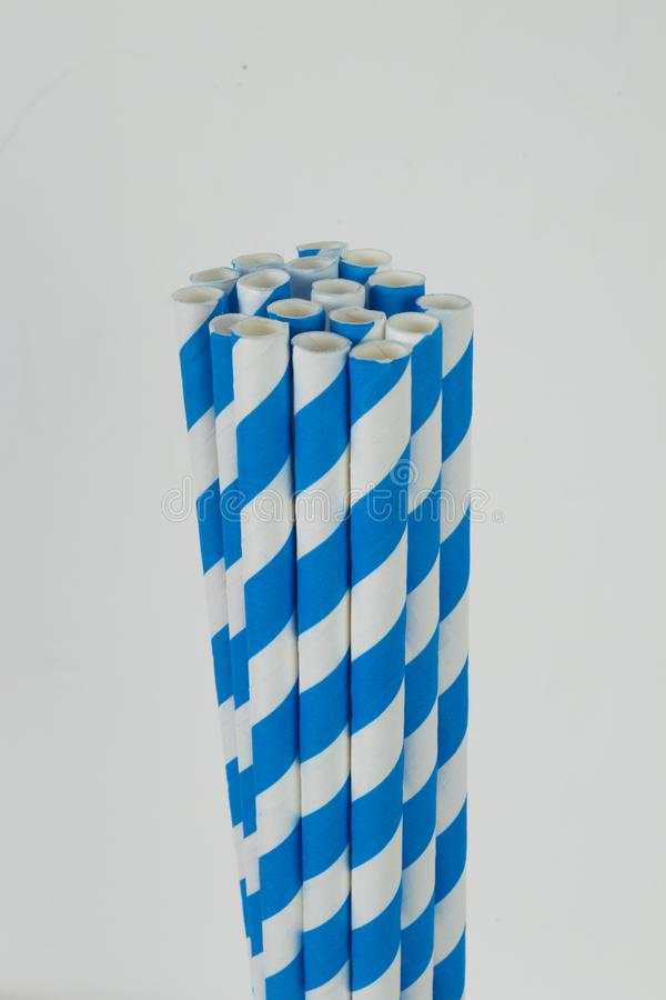 Paper straws in a vertical format on a white background. Blue striped paper straws and ends in a vertical format against a white background royalty free stock photos