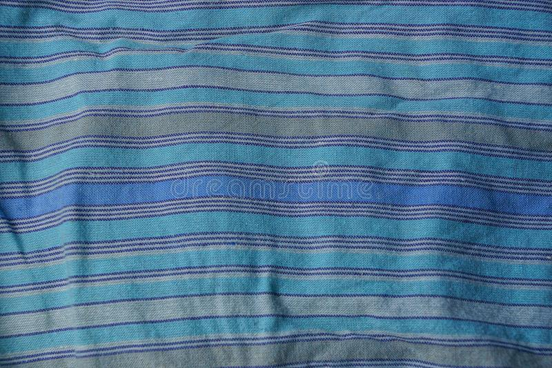Blue striped texture of a cloth from a piece of crumpled clothes stock images