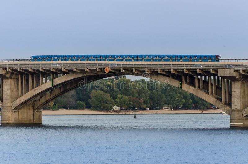 The blue subway train rides along the bridge over the river royalty free stock images
