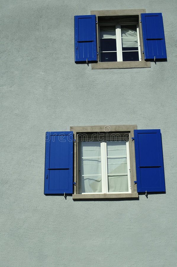 Blue suhtters. Bright blue shutters on a grey wall. Space for text at the base of the image stock photo