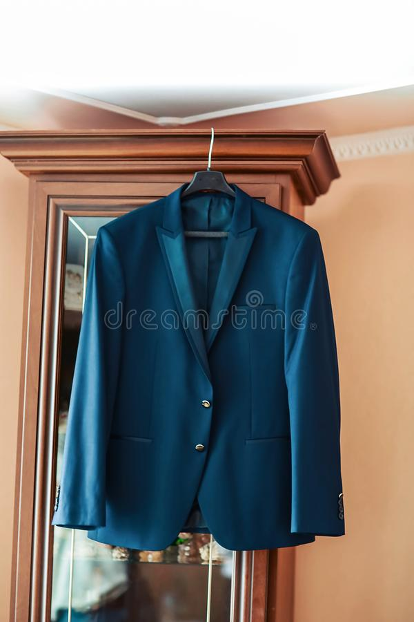 Blue suit that hangs on the wall, clothes for the groom in the room, a set of classic men`s clothing, accessories for the groom royalty free stock image
