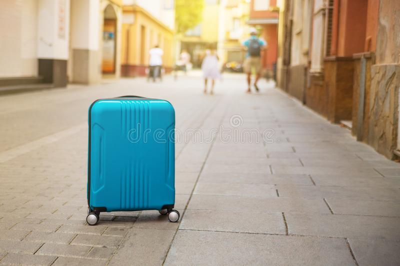 Blue suitcase on European city street, tourism in Europe Copy space stock images