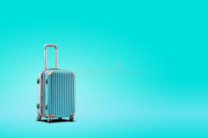 Blue suitcase is standing against turquoise background. A realistic shadow is drawn in under it. Collage. Copy space. For your text or images, close-up royalty free stock photo