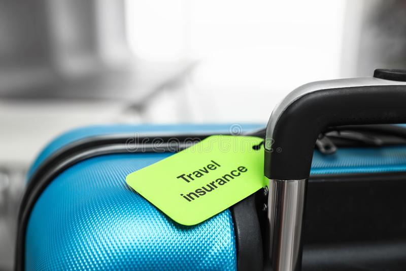Blue suitcase with TRAVEL INSURANCE label indoors royalty free stock photography
