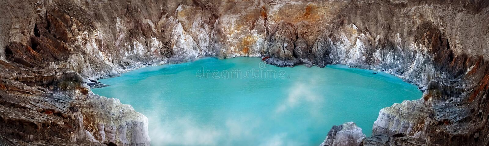Blue sulfur toxic lake in the crater of the Ijen volcano. Poisonous sulfur smoke. stock photography