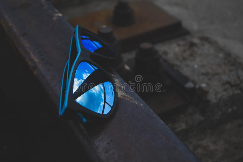 Blue sunglasses, close-up, lie on the rails. There is a place for text. Copy space royalty free stock photography