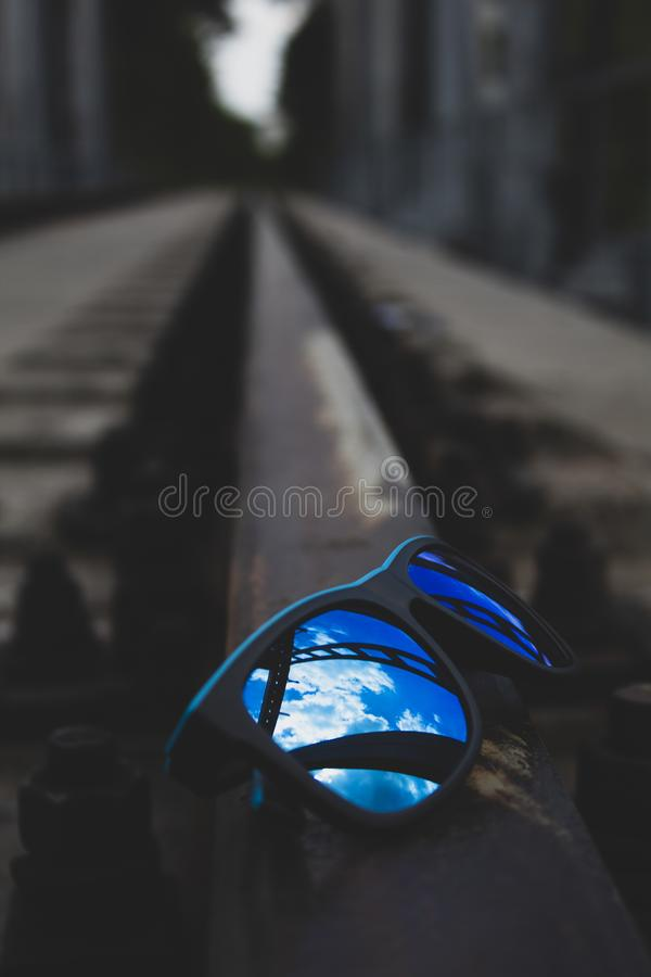 Blue sunglasses, close-up, lie on the rails. There is a place for text. Copy space royalty free stock photo