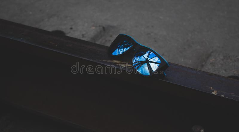 Blue sunglasses, close-up, lie on the rails. There is a place for text. Copy space stock images