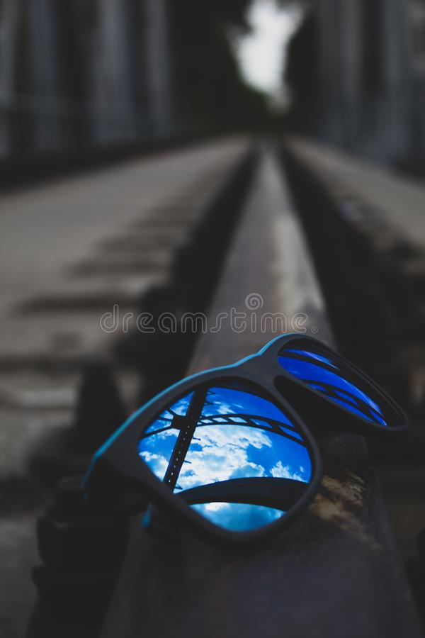Blue sunglasses, close-up, lie on the rails. There is a place for text. Copy space royalty free stock image