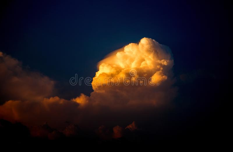 Blue sunset sky and bright yellow cloud. Last ray of sunlight on fluffy cloud. Vivid tropical sunset sky. Yellow orange sunlight on cumulus. Romantic skyscape stock photo