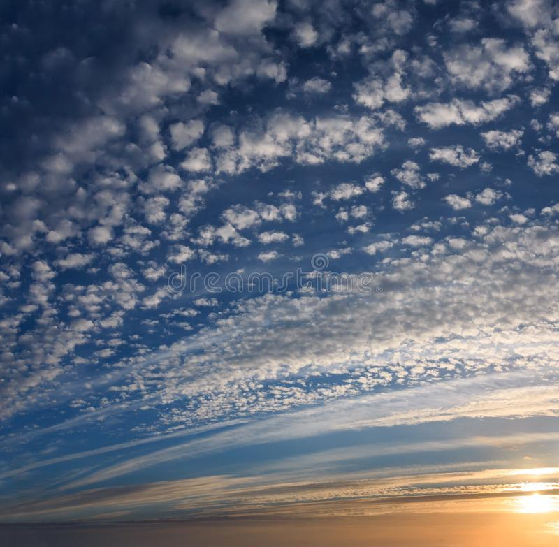 Blue sunset sky with clouds background. Summer evening sunset sky with fleece and spindrift clouds and sunshine background royalty free stock photo