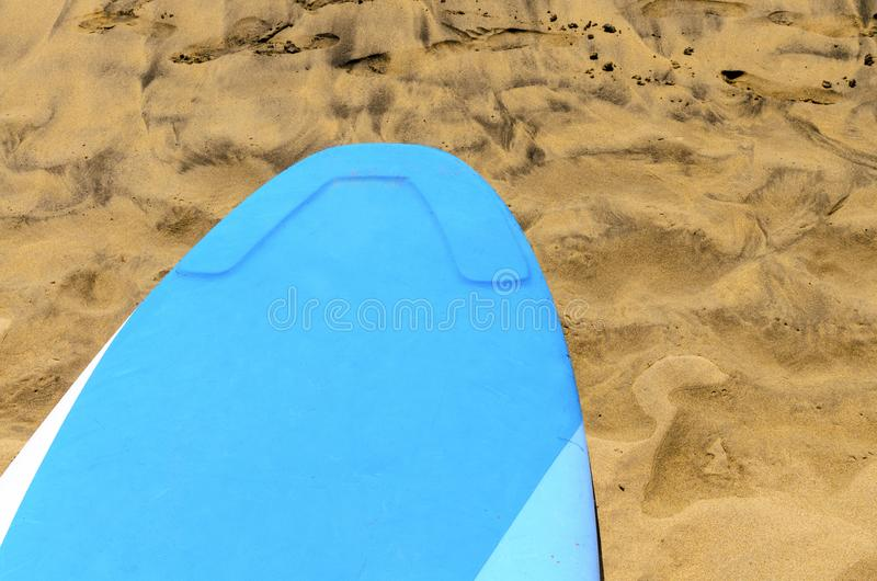 Blue surf plank in the sand royalty free stock image