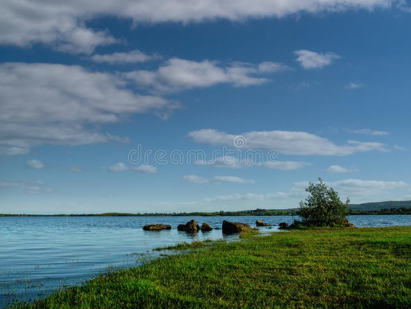 Blue surface of lake Corrib and cloudy sky, Grass covers shore. Warm sunny day.  royalty free stock photo