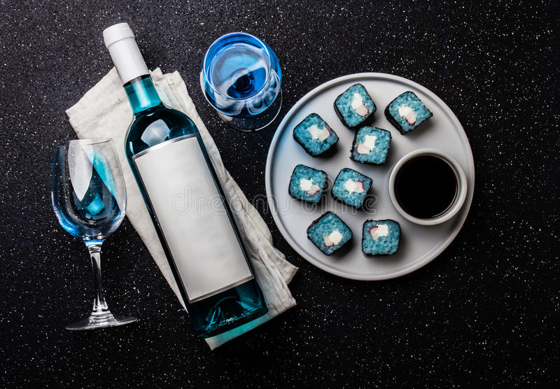 Blue sushi rolls and blue wine chardonnay on black background. Spanish blue wine, trendy drink, Fancy wine, top view royalty free stock photography