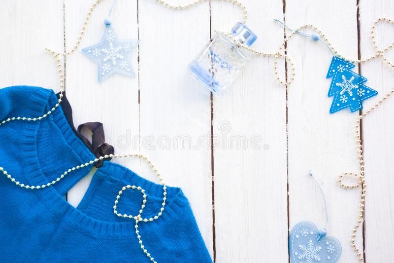 Blue sweater on a white wooden background with new-year decorations. New Year`s decor. Winter background in pink colors. Winter c. Oncept stock image