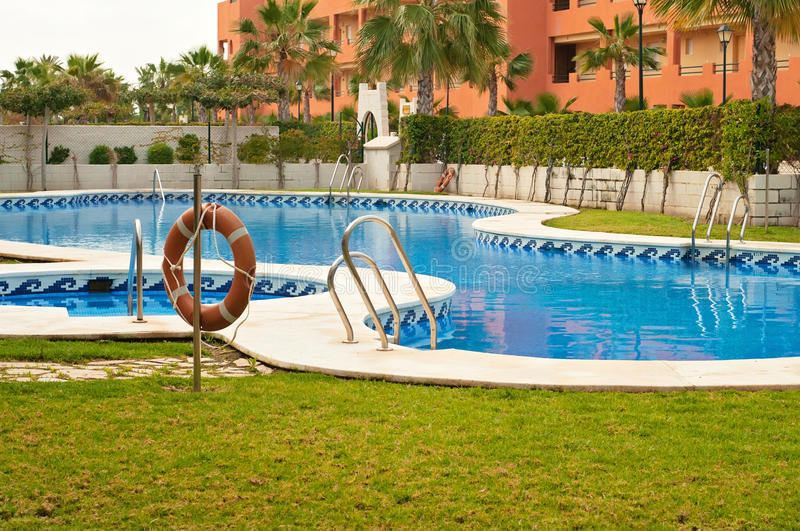 Blue swimming pool and orange lifebelt. In residental area stock photography