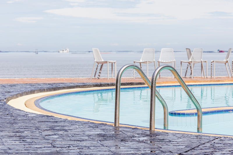Blue swimming pool with relaxing beach chairs in background. royalty free stock images