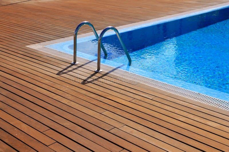 Blue Swimming Pool With Teak Wood Flooring Stock Image