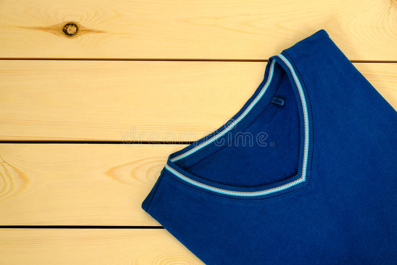 Blue t-shirt on wooden background royalty free stock photo