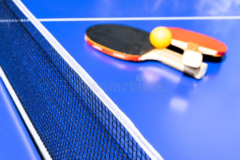 Blue table tennis or ping pong. Close-up ping-pong net. Close up ping pong net and line. Two table tennis or ping pong rackets or royalty free stock photos